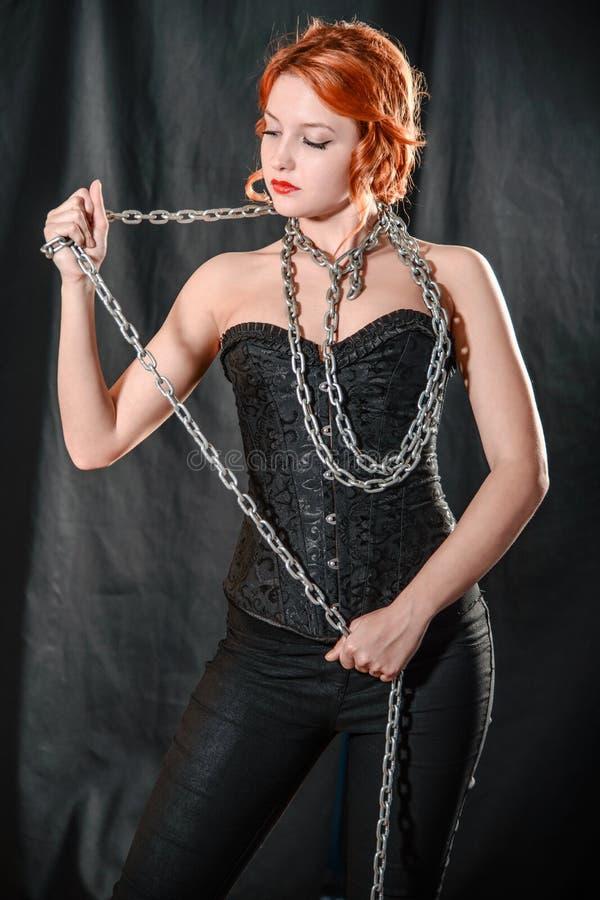 Jeune fille de forme physique posant avec la grande chaîne autour du cou image libre de droits