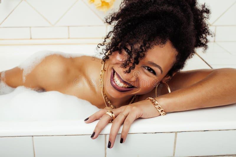 Jeune fille de l'adolescence afro-américaine s'étendant dans le bain avec la mousse, bijoux de port de butin impeccables, faisant images stock