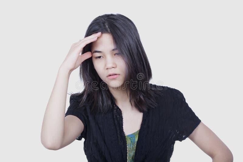 Jeune fille de l'adolescence biracial massant le temple, soumis à une contrainte, photos libres de droits