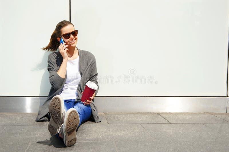 Jeune fille de l'adolescence heureuse à l'aide d'un téléphone intelligent au-dessus de mur dans le backg photo libre de droits