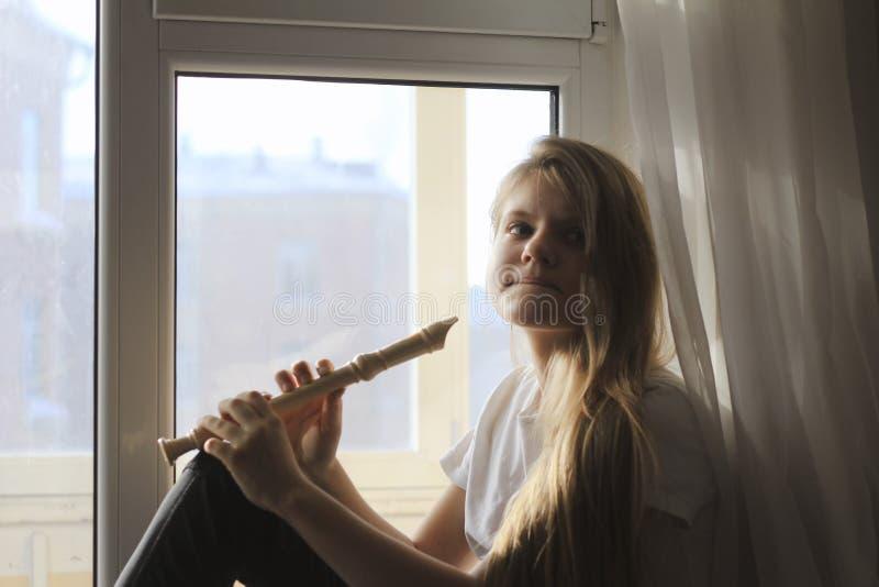 Jeune fille de l'adolescence mignonne jouant sur la cannelure se reposant sur le rebord de fenêtre à la maison photos stock