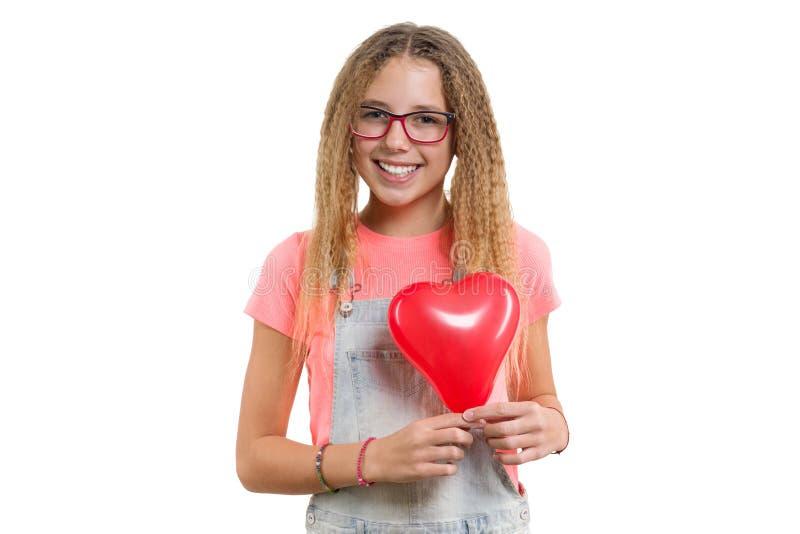 Jeune fille de l'adolescence de sourire félicitant en vacances avec le ballon rouge de coeur sur le fond blanc d'isolement image stock