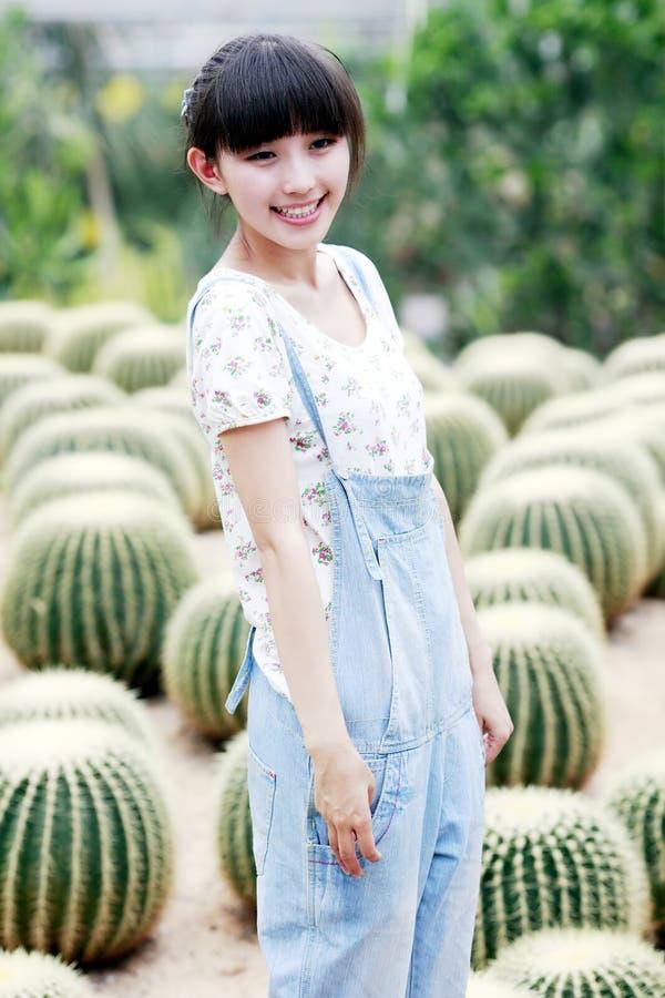 Jeune fille de l'Asie dans le domaine de cactus. images libres de droits