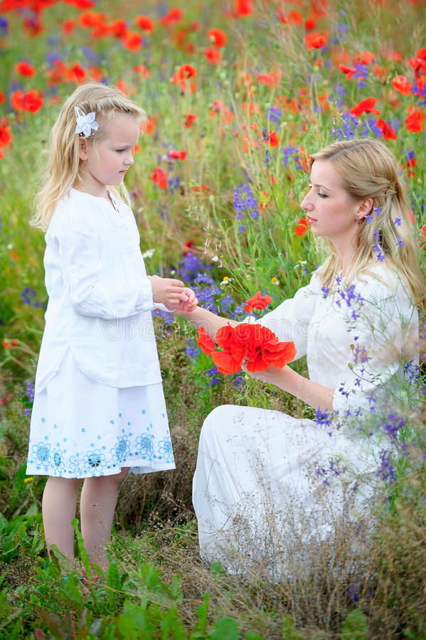 Jeune fille de mère et d'enfant dans des robes de blanc sur le pré d'été Dau images stock