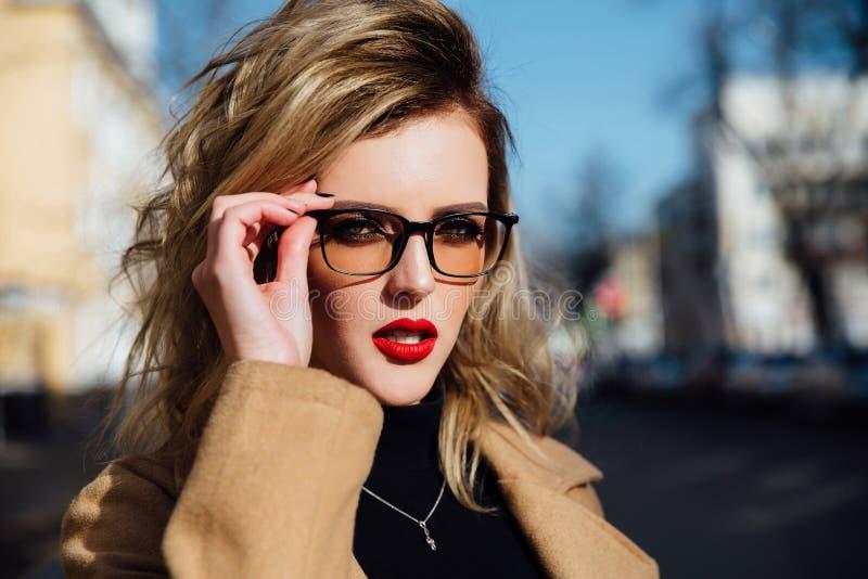 Jeune fille de mode en verres Lèvres blondes et rouges, manteau beige marchant le long de la rue de ville images libres de droits
