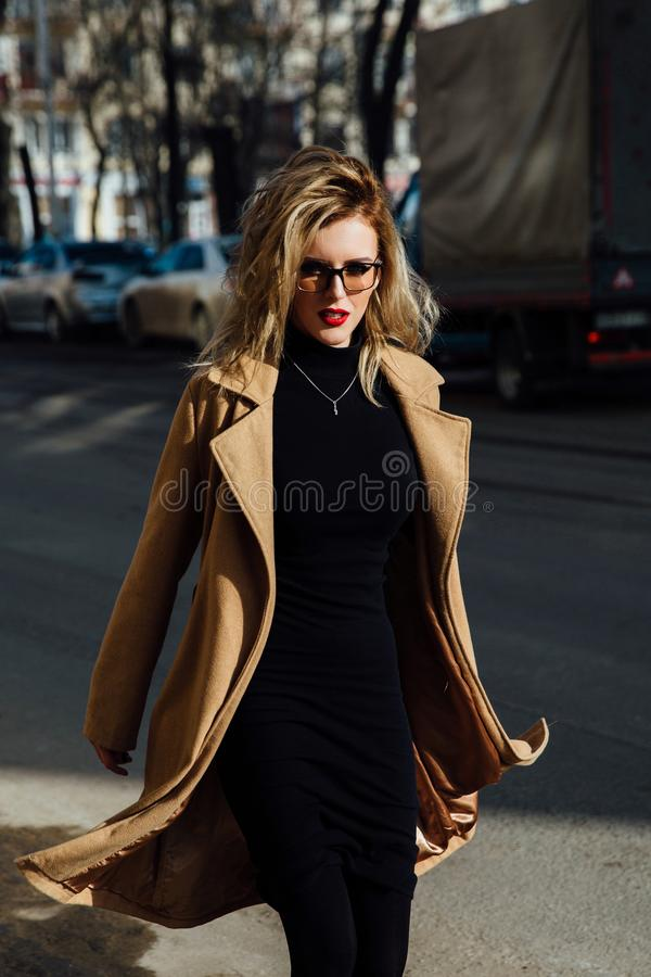 Jeune fille de mode en verres Lèvres blondes et rouges, manteau beige marchant le long de la rue de ville images stock