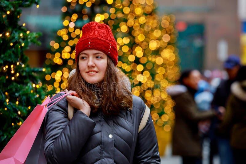 Jeune fille de mode de portrait haut étroit de mode de vie, avec des sacs à provisions marchant du magasin, fond coloré de bokeh  photos stock