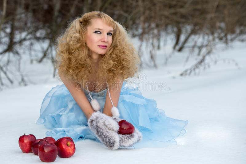 Jeune fille de neige dans une forêt de l'hiver avec des pommes images stock