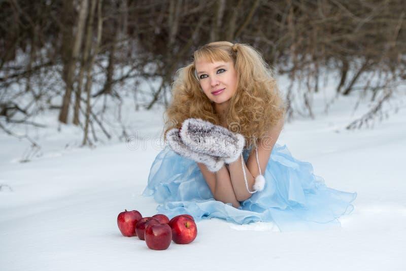 Jeune fille de neige dans une forêt de l'hiver avec des pommes photographie stock