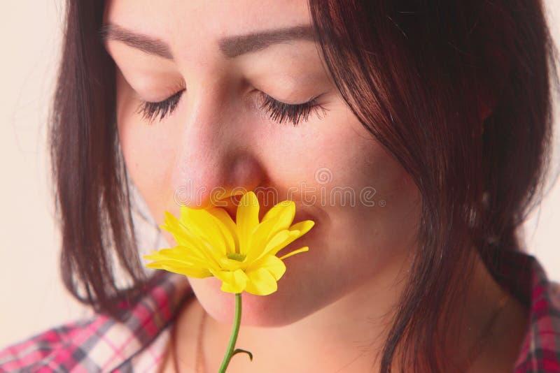 Jeune fille de portrait sentant la fleur jaune images stock