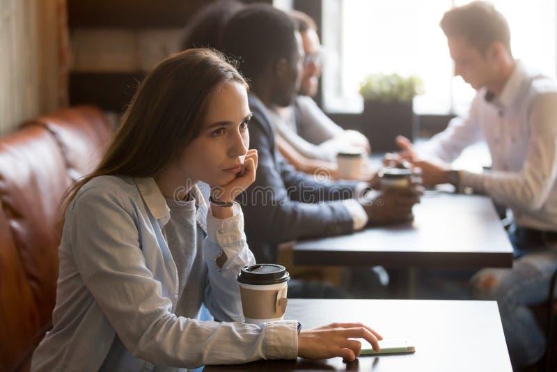 Jeune fille de renversement songeur seul s'asseyant à la table en café photo libre de droits