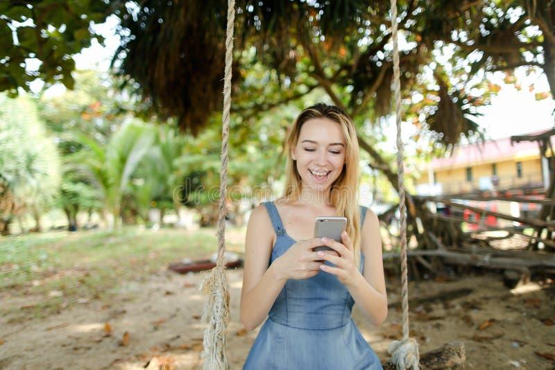 Jeune fille de sourire à l'aide du smartphone et mettant en oeuvre les réseaux sociaux, oscillation de monte sur le sable photographie stock libre de droits