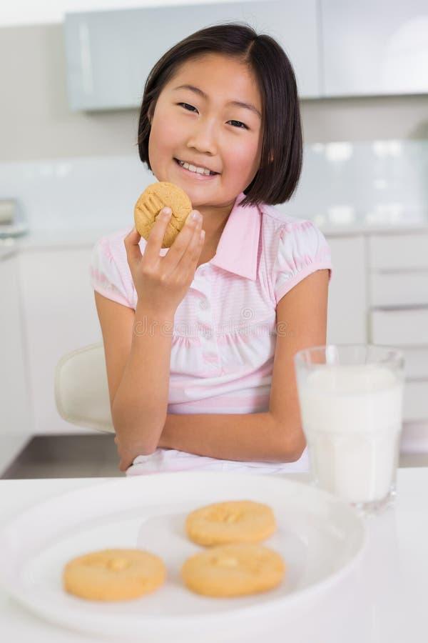 Jeune fille de sourire appréciant les biscuits et le lait photos stock