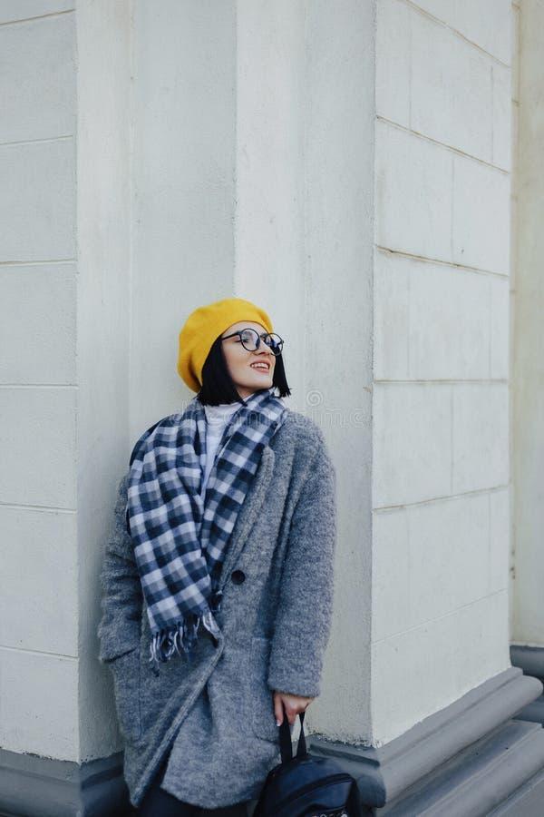 Jeune fille de sourire attirante en verres dans le manteau et le b?ret jaune sur un fond clair simple images stock