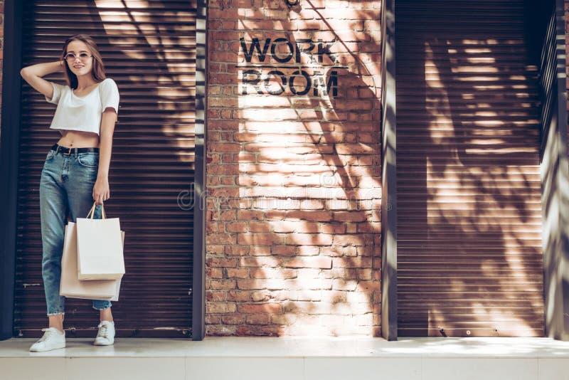 Jeune fille de sourire avec le T-shirt et les blues-jean blancs de port de sac à provisions près du mur de briques Concept de mod photographie stock libre de droits