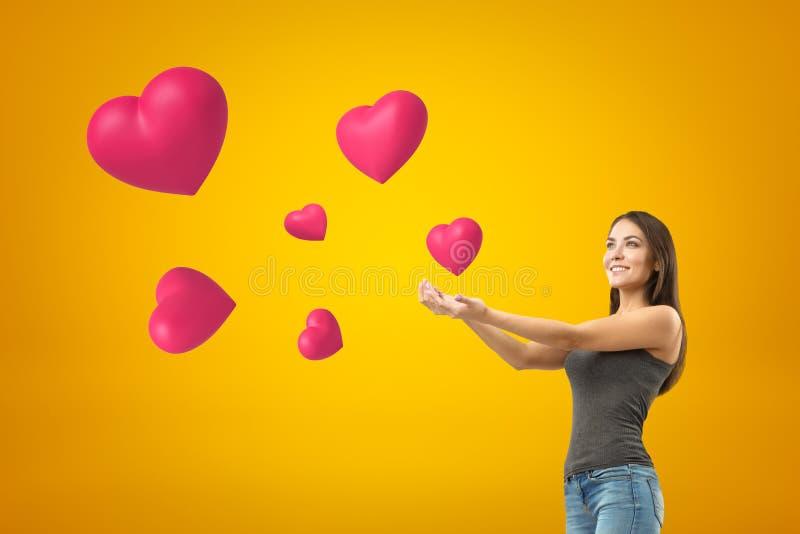 Jeune fille de sourire de brune utilisant les jeans et le T-shirt occasionnels avec des paumes et des coeurs roses sur le fond ja image libre de droits