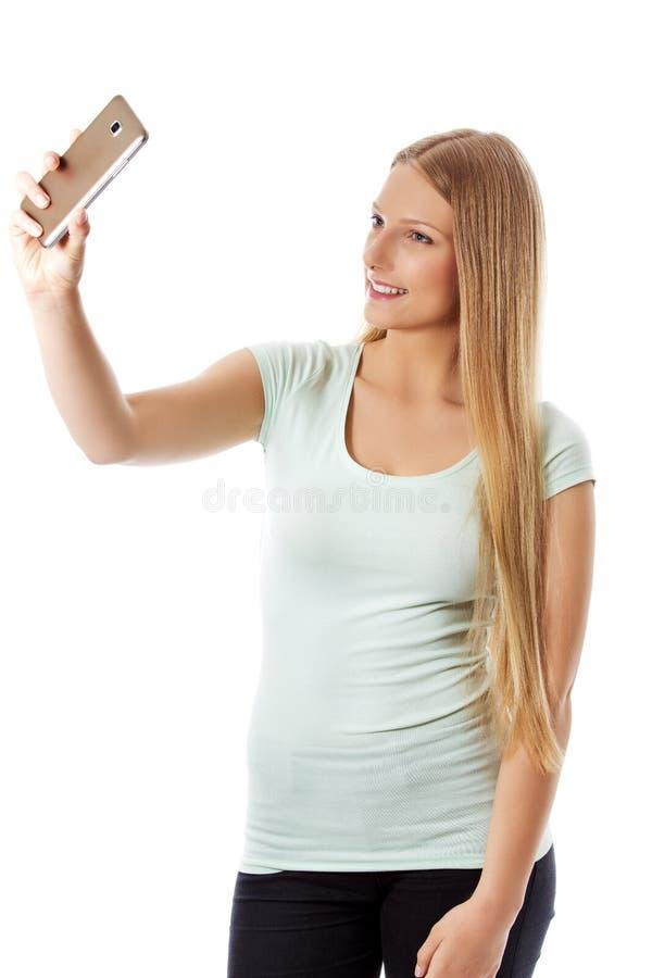 Jeune fille de sourire faisant la photo de selfie d'isolement sur un blanc images libres de droits