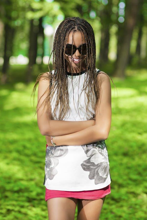 Jeune fille de sourire heureuse d'adolescent d'Afro-américain avec l'abondance de longs Dreadlocks posant dans des lunettes de so photo stock