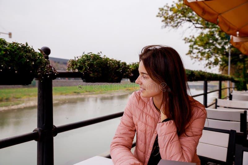 Jeune fille de sourire heureuse dans un café Belle fille dans des couleurs à la mode d'automne photographie stock