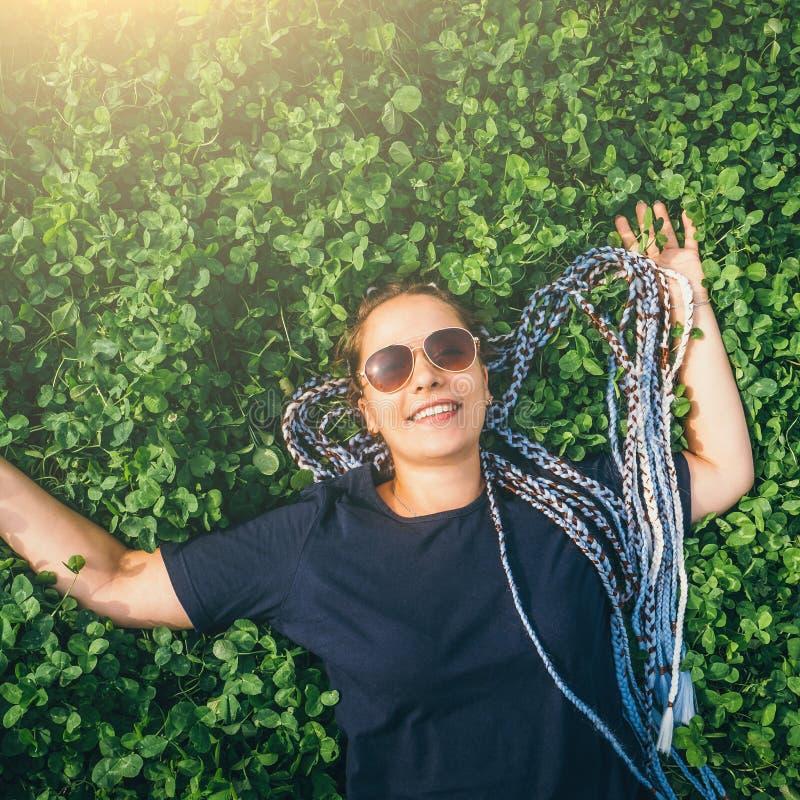 Jeune fille de sourire heureuse insouciante avec les cheveux tressés se situant dans le pré de trèfle ou l'herbe verte, vue supér images stock