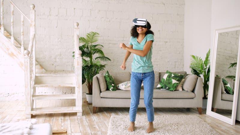 Jeune fille de sourire heureuse de métis obtenant l'expérience utilisant des verres de casque de VR de réalité virtuelle et dansa photos stock