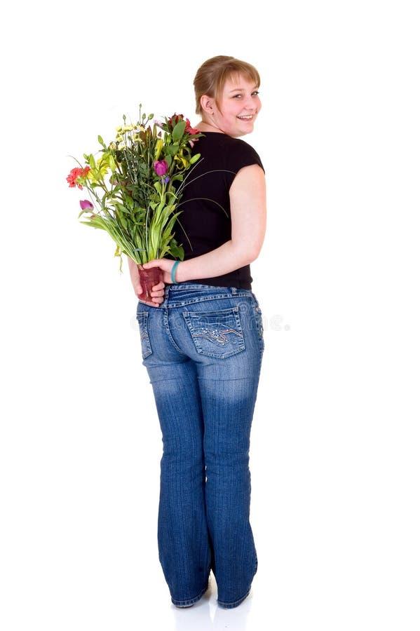 Jeune fille de sourire heureuse présent des fleurs photo libre de droits