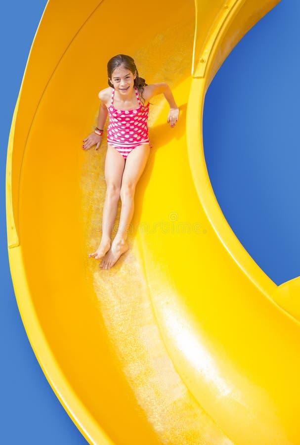 Jeune fille de sourire montant en bas d'une glissière d'eau jaune photographie stock libre de droits