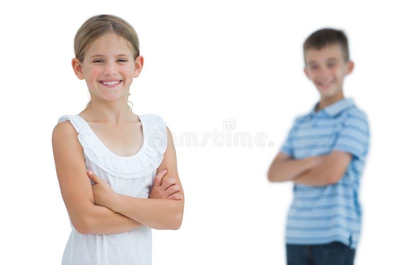 Jeune fille de sourire posant avec son frère images libres de droits