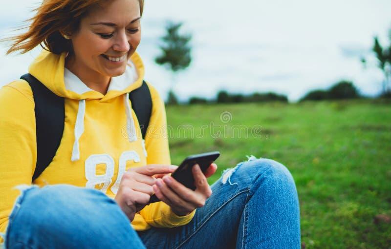 Jeune fille de touristes de sourire sur l'herbe verte de fond utilisant le smartphone mobile, femmes se tenant en technologie fem photos libres de droits