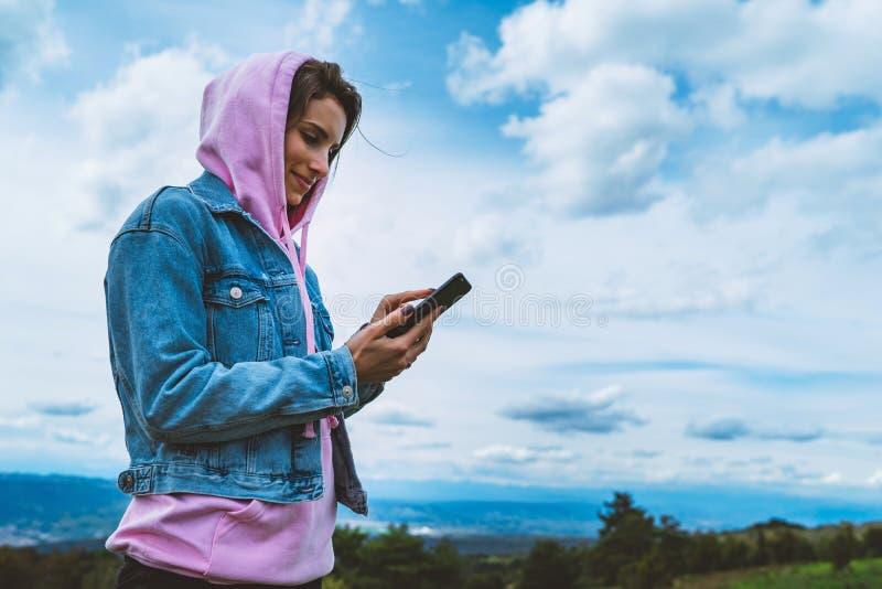 Jeune fille de touristes sur le ciel bleu de fond utilisant le smartphone mobile, participation de personne dans le doigt femelle images stock