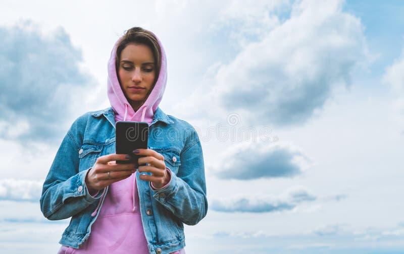Jeune fille de touristes sur le ciel bleu de fond utilisant le smartphone mobile, participation de personne en technologie femell images stock