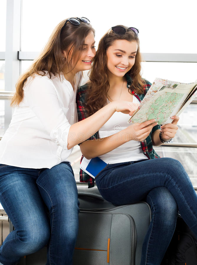 Jeune fille deux aux cheveux foncés regardant la carte photos libres de droits