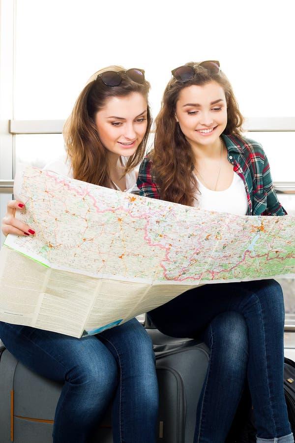 Jeune fille deux aux cheveux foncés regardant la carte photos stock