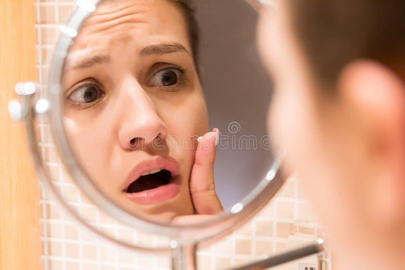 Jeune fille devant un miroir de salle de bains mettant la cr?me sur un bouton rouge Soins de la peau de beaut? et concept de mati images libres de droits