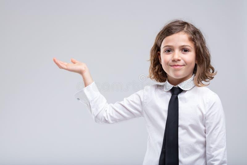 Jeune fille donnant sa paume vide avec un sourire photo stock