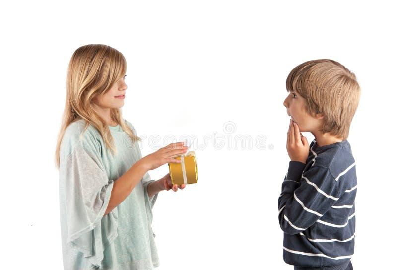 Jeune fille donnant un cadeau à un garçon photographie stock libre de droits
