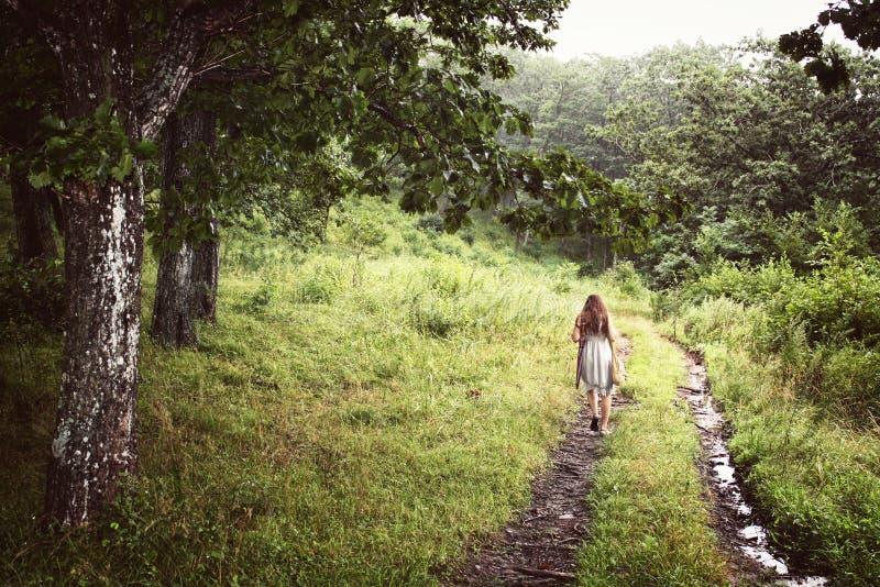 Jeune fille du dos dans une robe seul marchant dans la forêt photos stock