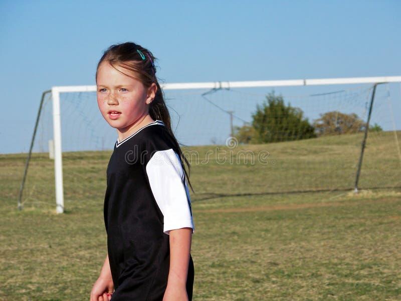 Jeune fille du football sur le champ pendant un jeu photo libre de droits