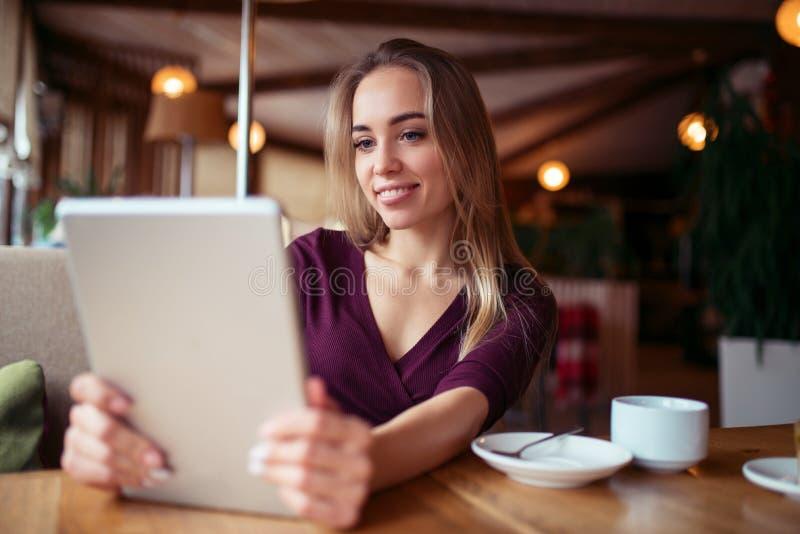 Jeune fille employant 4g sur le comprimé en café images libres de droits