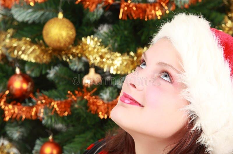 Jeune fille en arbre de capuchon et de Noël de Santa images stock