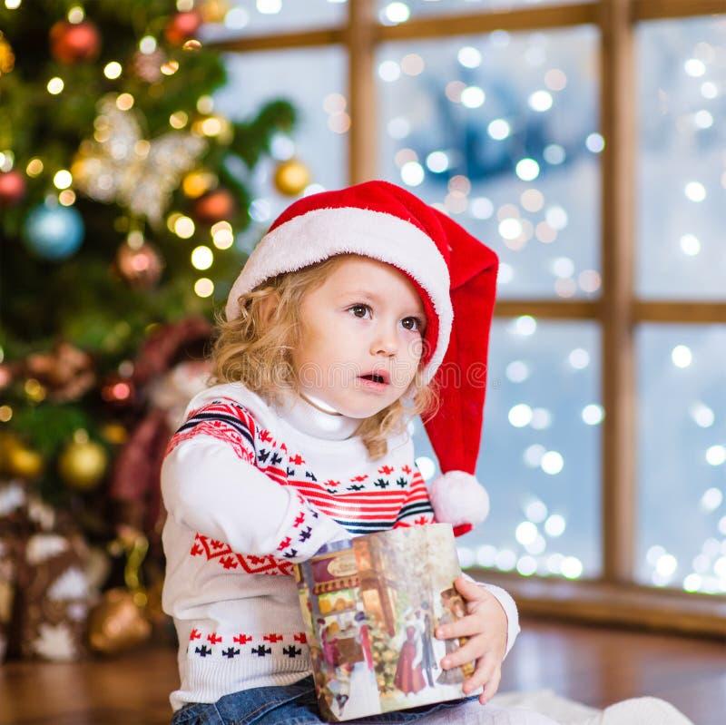 Jeune fille en cadeaux rouges de Noël d'ouverture de chapeau de Santa photographie stock