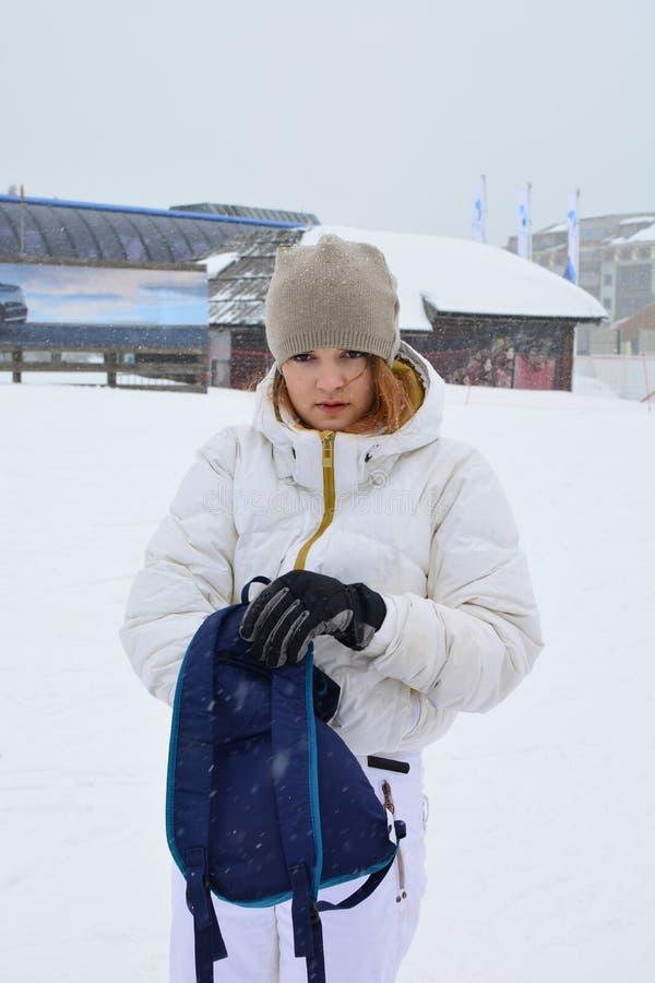 Jeune fille en costume de ski blanc avec sac à dos bleu photos libres de droits
