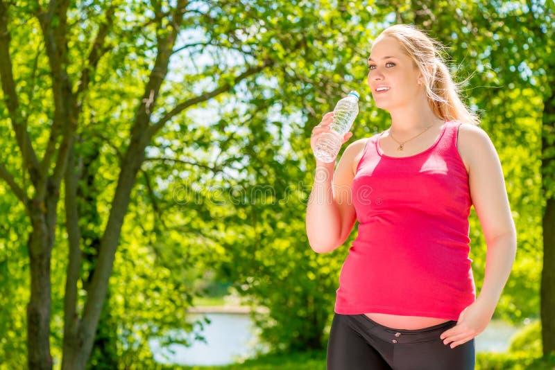 Jeune fille enceinte en bonne santé avec une bouteille de l'eau minérale image libre de droits