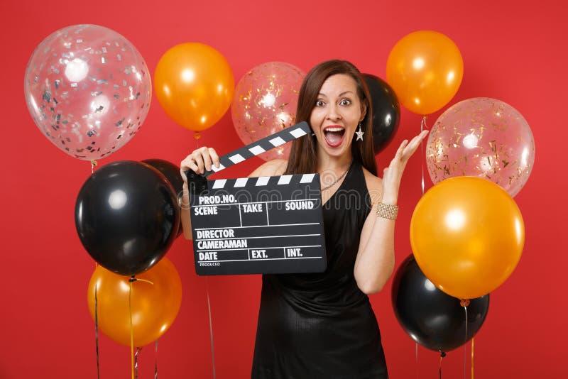 Jeune fille enthousiaste dans la robe noire célébrant les mains de propagation de claquette noire classique de cinéma de prise su images libres de droits