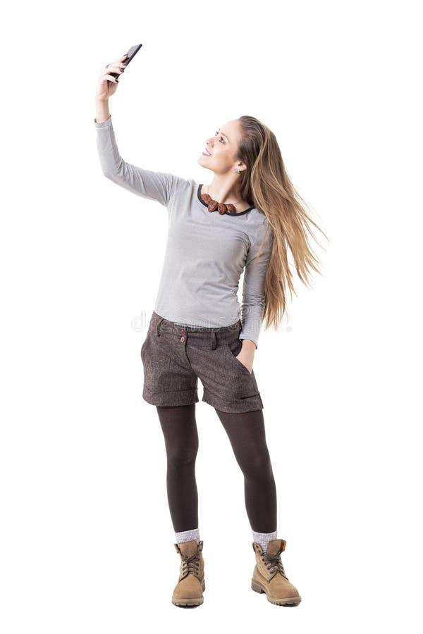 Jeune fille enthousiaste heureuse de hippie prenant le selfie et jetant les cheveux en l'air blonds longtemps débordants image libre de droits