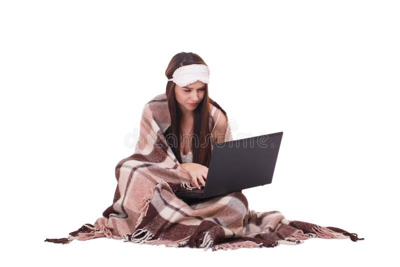Jeune fille enveloppée dans un plaid et avec un masque pour se reposer de sommeil et à l'aide d'un ordinateur portable D'isolemen images libres de droits