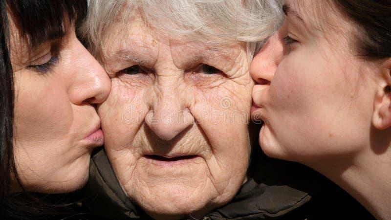 Jeune fille et femme adulte embrassant la grand-mère sur des joues, mamie souriant et regardant à l'appareil-photo Famille trois image libre de droits