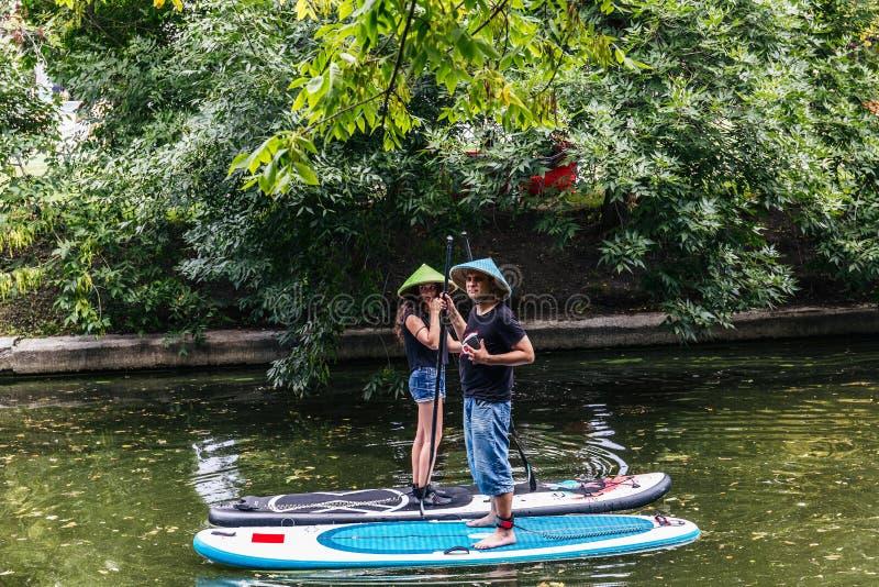 Jeune fille et homme dans des chapeaux de paille se tenant sur des planches de surf photos libres de droits