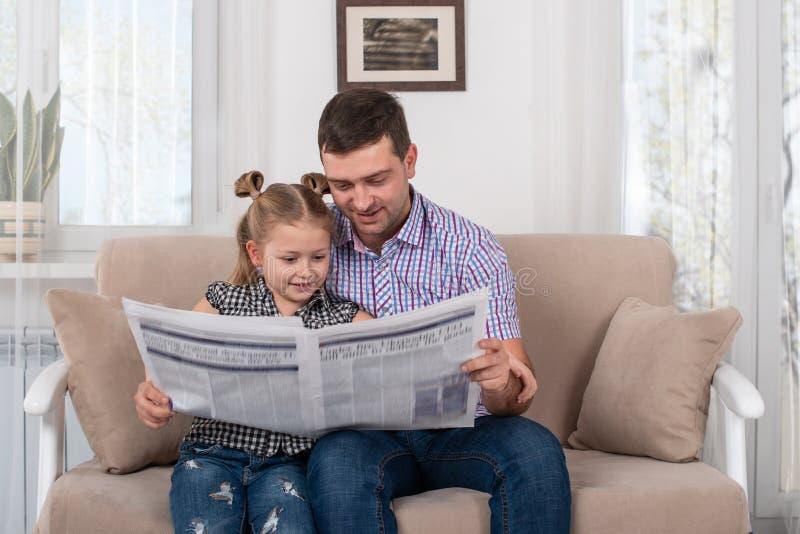 Jeune fille et papa s'asseyant sur le sofa à la maison et lisant le journal ensemble photographie stock libre de droits