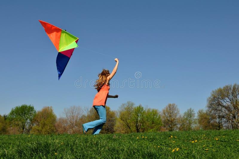 Jeune fille exécutant avec le cerf-volant images stock